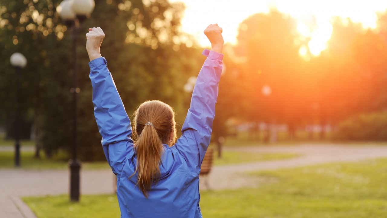 Successful woman runner raising arms to the sun