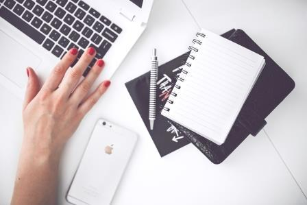 womans hand with laptop and smartphone