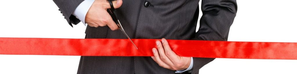 professional in a suit cutting a red ribbon