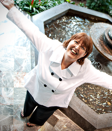 denise reed in a white suite in front of a fountain
