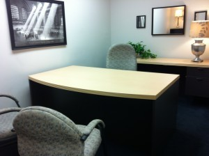 office space with desk and painting on wall