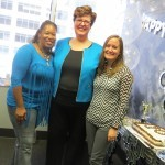 three women standing with a cake