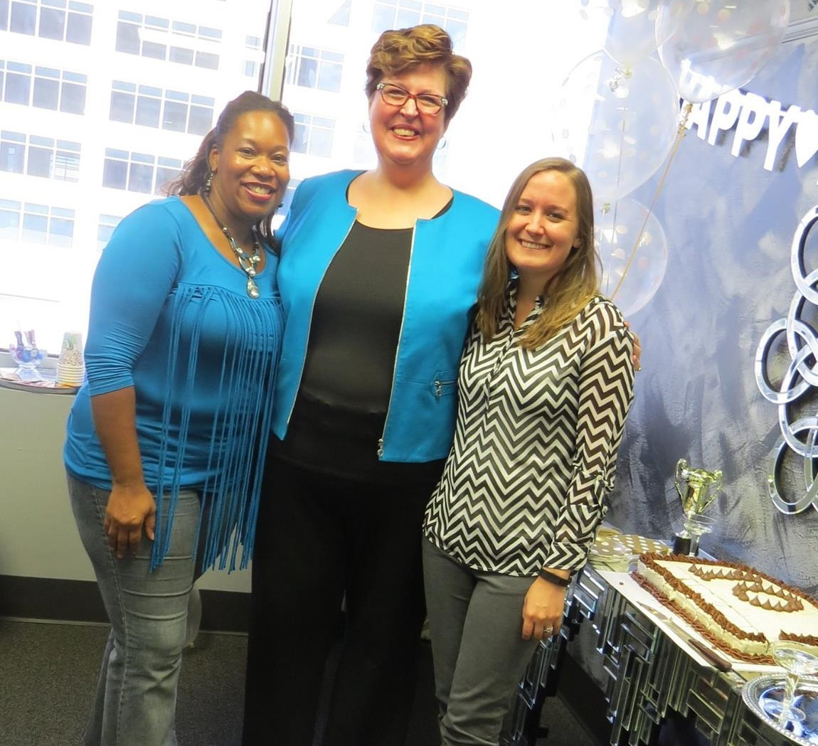 three women standing at a party with a cake