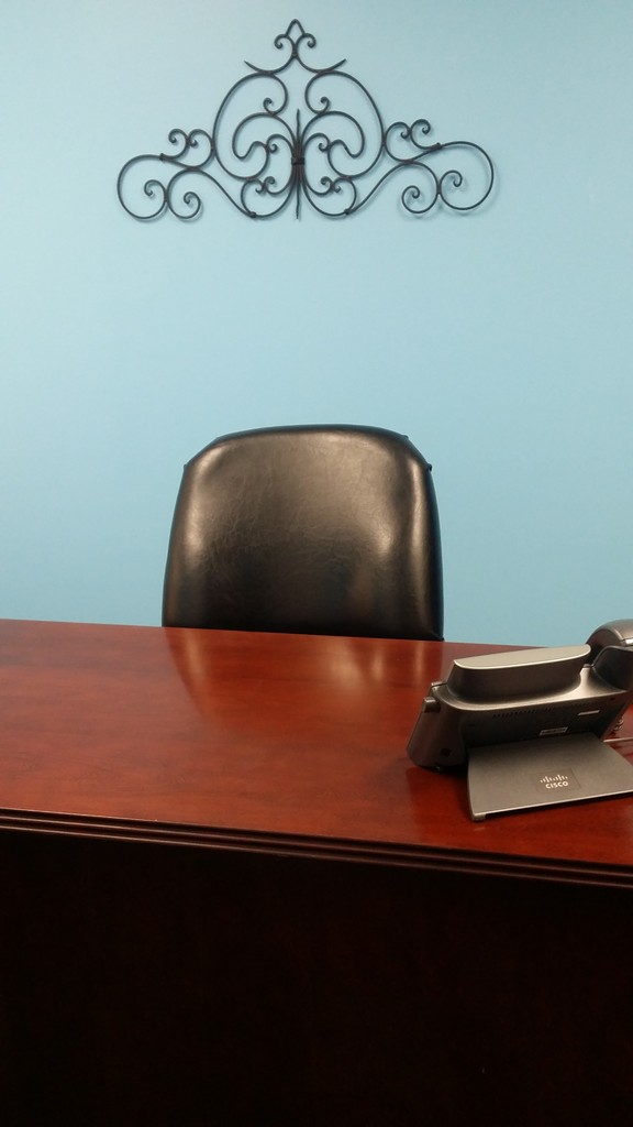 office with blue wall and a wooded desk and wall decor