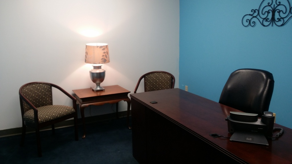 office space with blue wall, desk and table with two chairs