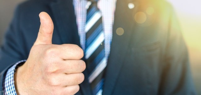 man in suite giving thumbs up with a blue tie
