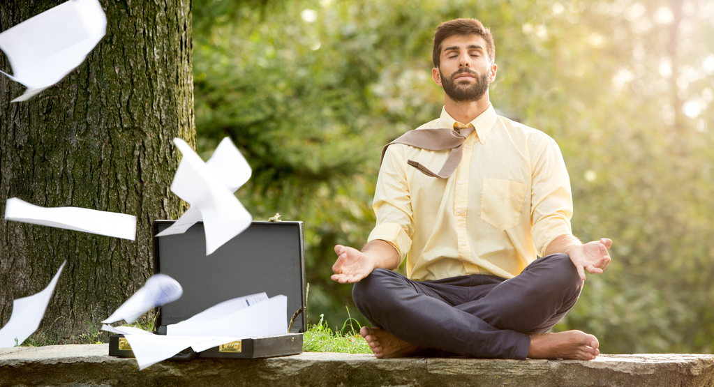 business man meditating while his papers fly away
